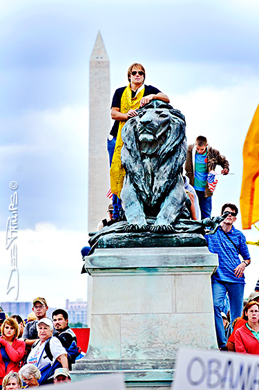 Youth climb onto a statue at the DC Tea Party.