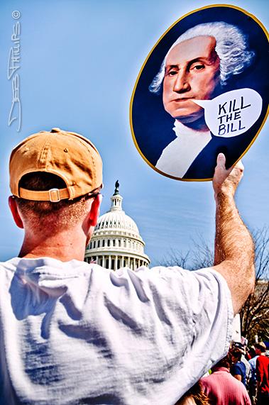 "A health-care protester raises a George Washington ""Kill the Bill"" sign outside the U.S. Capitol."
