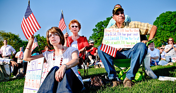 Tea Party attendees bring U.S. flags and original signs.