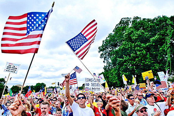 A crowd of friendly Americans lift their flags and voices at the Washington, DC Tea Party.