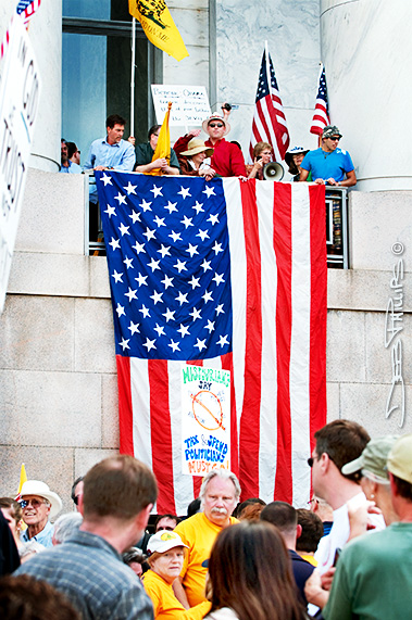 """Americans draped a flag over the railing at the Rayburn House Office Building after the """"Kill the Bill"""" rally on the grounds of the U.S. Capitol on 3/20/10."""