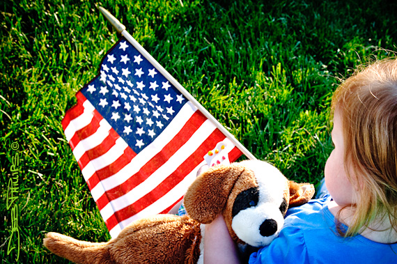 A small child holds a U.S. flag and a stuffed friend at the Tea Party rally.
